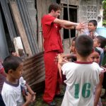 Volunteer Teaching Children How to Stretch in Panama