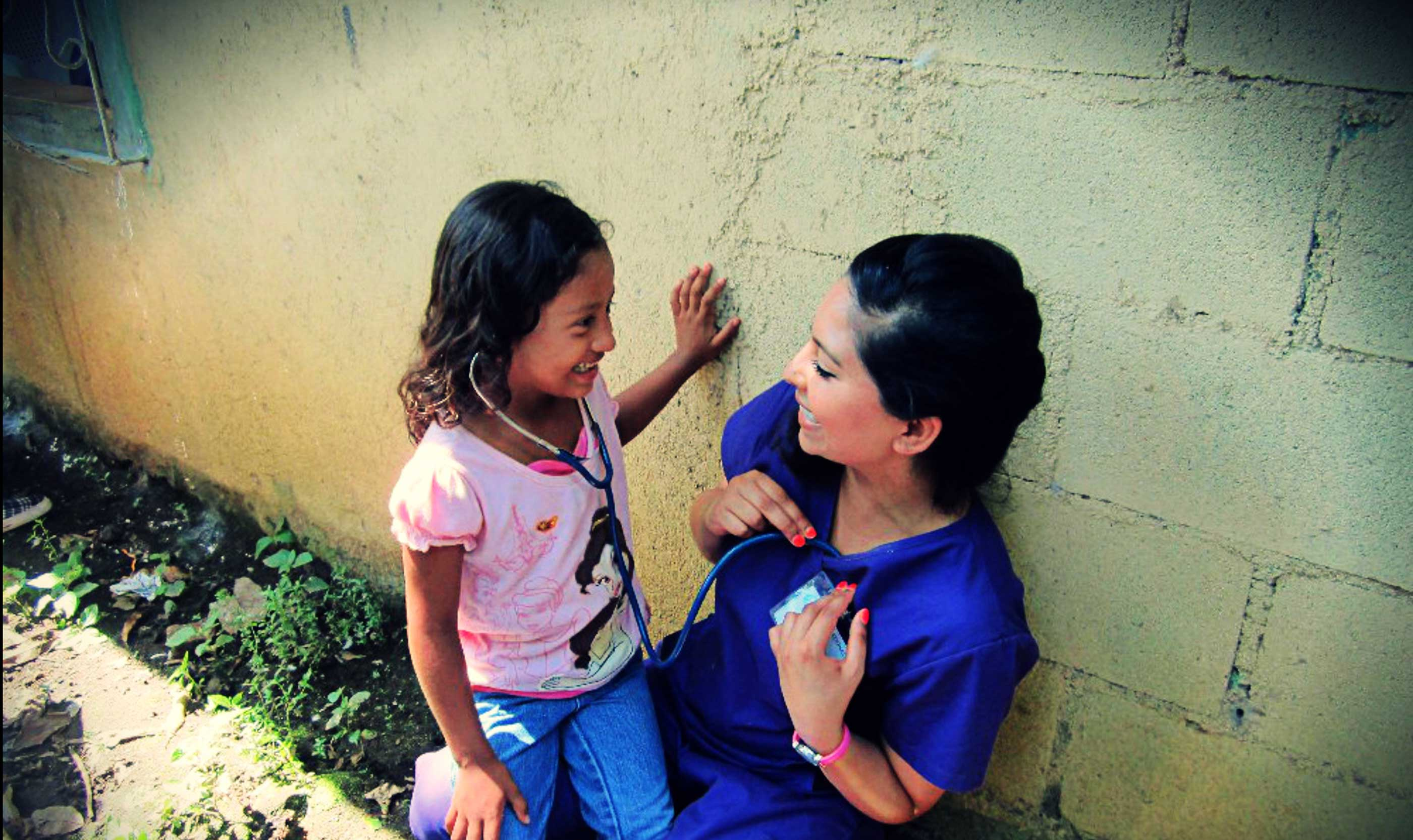 A volunteer shares her heartbeat via a stethoscope with a child.